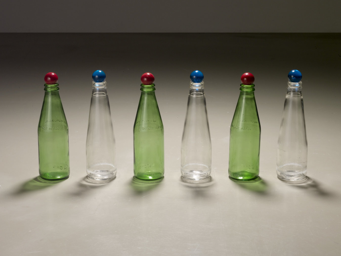 ", 2007. Glass bottles, glass marbles, 8"" x 20"" x 2"" (20.3 cm x 50.8 cm x 5.1 cm)."