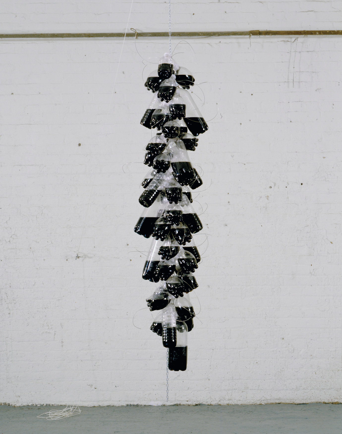 ", 2007. Plastic bottles with screw caps, india ink, water, stainless steel wire, chain, 84"" x 16"" diameter (213.4 cm x 40.6 cm)."