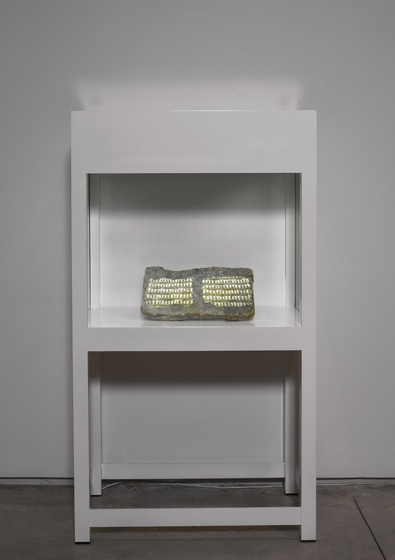 ", 2004. steel vitrine with glass, stone and video projection, 57-1/8"" x 32"" x 20"" (145.1 cm x 81.3 cm x 50.8 cm)."