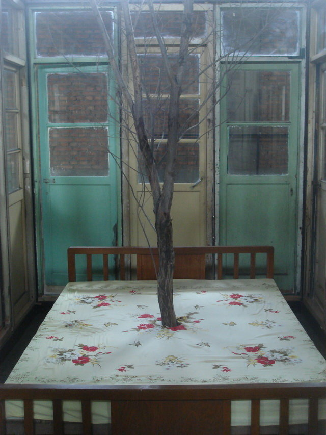 . Steel pipe, wooden door, wooden bed, withered tree, bed sheets, 392 x 245 x 265 cm; bed size: 150 x 200 x50cm; tree height: 500cm .