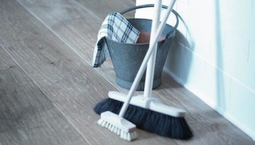 a broom, scrubber brush and metal bucket are ready for use