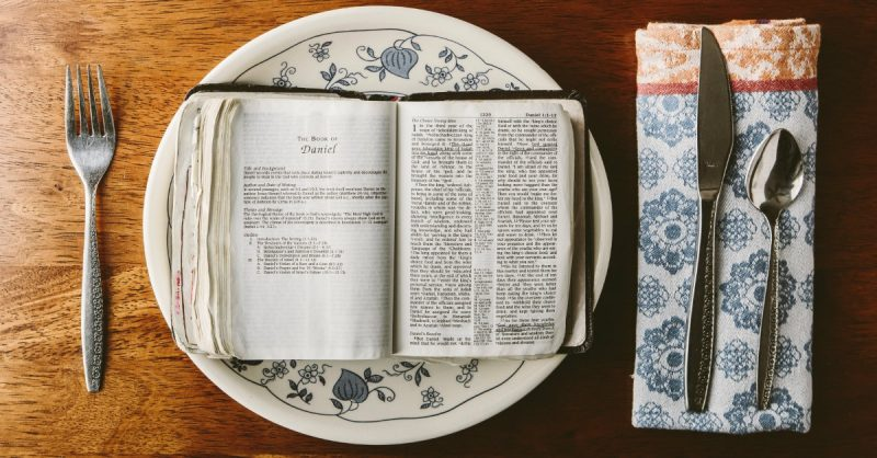 A dinner plate with an open Bible on it and silverware on the sides