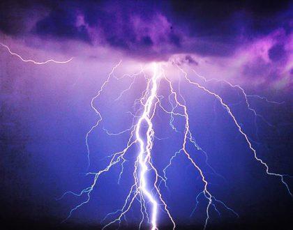 A brilliant flash of lightning illuminates a dark violet blue sky