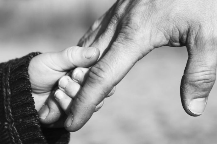 a small child's hand holds to the finger of a man