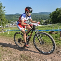 Kate Courtney races up a hill at the 2014 UCI MTB World Cup in Windham, N.Y.