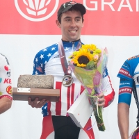 Eric Young smiles on the podium