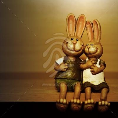 Zwei glückliche lächelnde Osterhasen sitzen auf Tisch