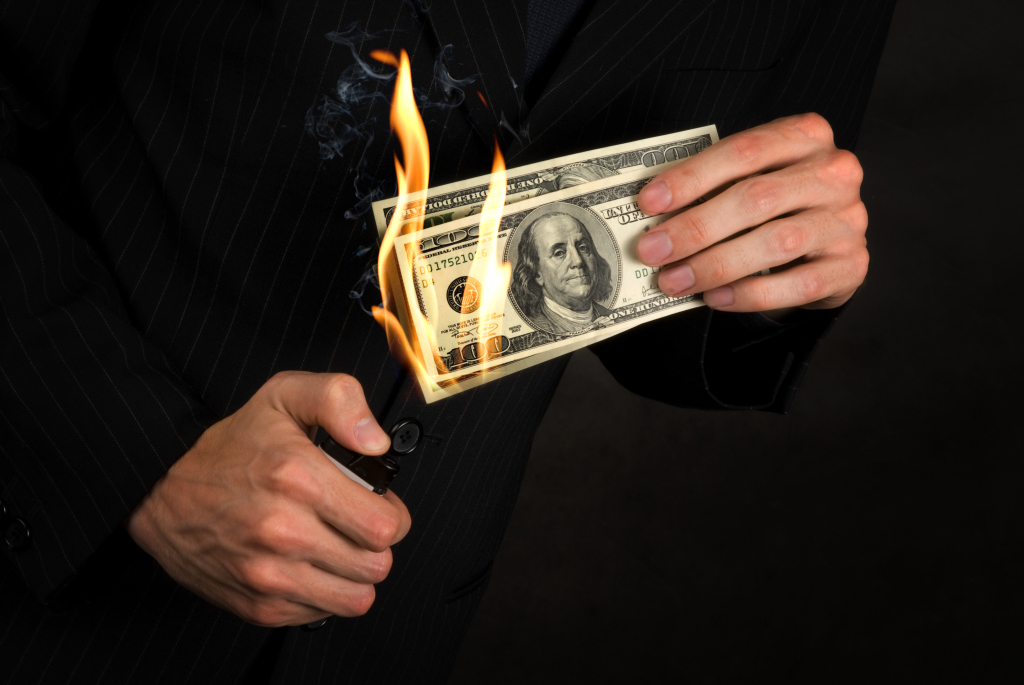 Flaming money in a hand