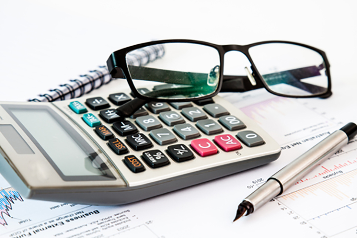 a calculator, pen, and a pair of glasses on top of paper