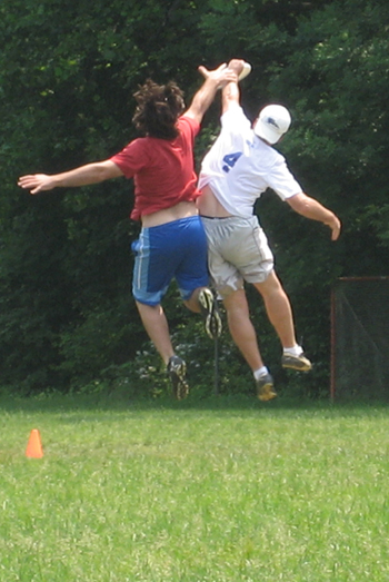 Two PADA players jump for a disc in the end zone.