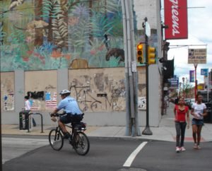 Police officer patrols near Sixth and South Streets.