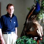 Craig Mann, owner of Mann Funeral Home located at 219 W Tabor Road in Olney, stands with his stuffed peacock, Peter.