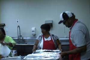 Alice McBride (center) and others prepare meals for their church's weekly food and prayer service.