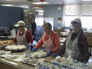 Volunteers help serve the meal of the day which is funded through Philadelphia Corporation for Aging.