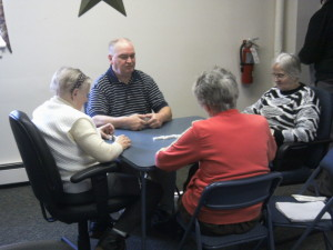 A group of Polish members enjoy playing games in the back room which also has exercise bikes and computers.