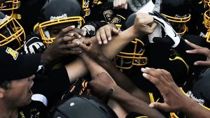 A mass of hands formed around coach Erb's as the Kensington football family rallied together during a game.