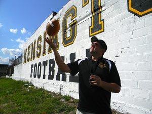 Kensington High School football coach Ellwood Erb stood in front of the wall he and his father painted by hand earlier this summer.