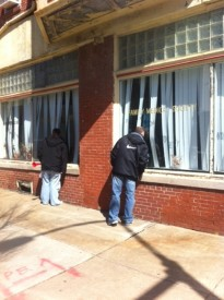 Two men peer into the former Family Medical Center at 3801 Lancaster Ave., the site where Dr. Kermit Gosnell allegedly performed illegal partial-birth abortions.