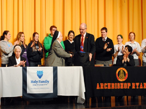 Holy Family President, Francesca Olney (left), exchanges gifts with Archbishop Ryan President Michael McArdle. Photo courtesy of Archbishop Ryan High School.