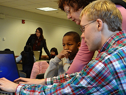 Dr. Diane Adler shows Michael Whitworth how to access the online education program as a student watches.