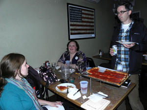 Local residents enjoy pizza while discussing community initiatives at the LoMo fundraiser event.
