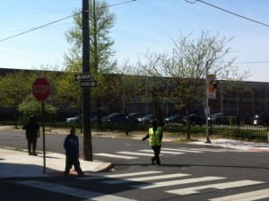 A crossing guard directs students across 35th Street and Fairmount Avenue.