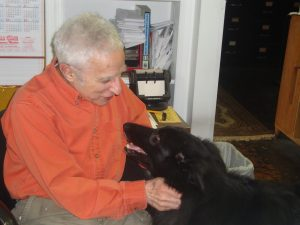 Alan Kringman played with his dog, Pluto, in his office on the 200 block of 46th street on April 18.