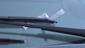 A strip of paper with the words of Psalm 18:2 sits underneath a windshield wiper in Fishtown