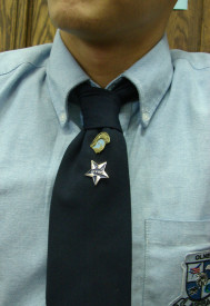 Frayby Peralta, a senior at Olney Charter High School, wears a Trojan pin on his uniform as a symbol of his high ranking in the student body.