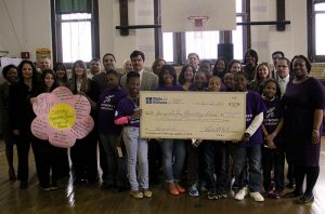 Spring Garden Elementary students stood with members of White and Williams Law firm to accept a $10,000 check to invest in their library.