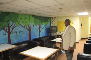 Reverend John Mosley explaining the mural in the basement of the Bainbridge House.