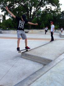 A skateboarder grinds a curb in Paine's Park.