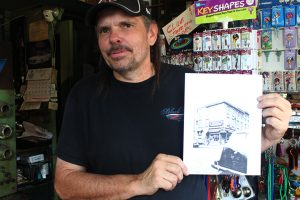 John Henssler posed with a picture of the original building from 1898.