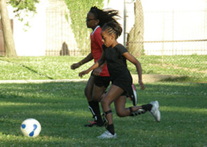 Two Soccer Sisters head to the goal during a warm-up drill
