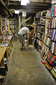 Tyler Lau sorts books in the basement storage area.