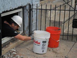 Volunteer lifted buckets out of basement window.