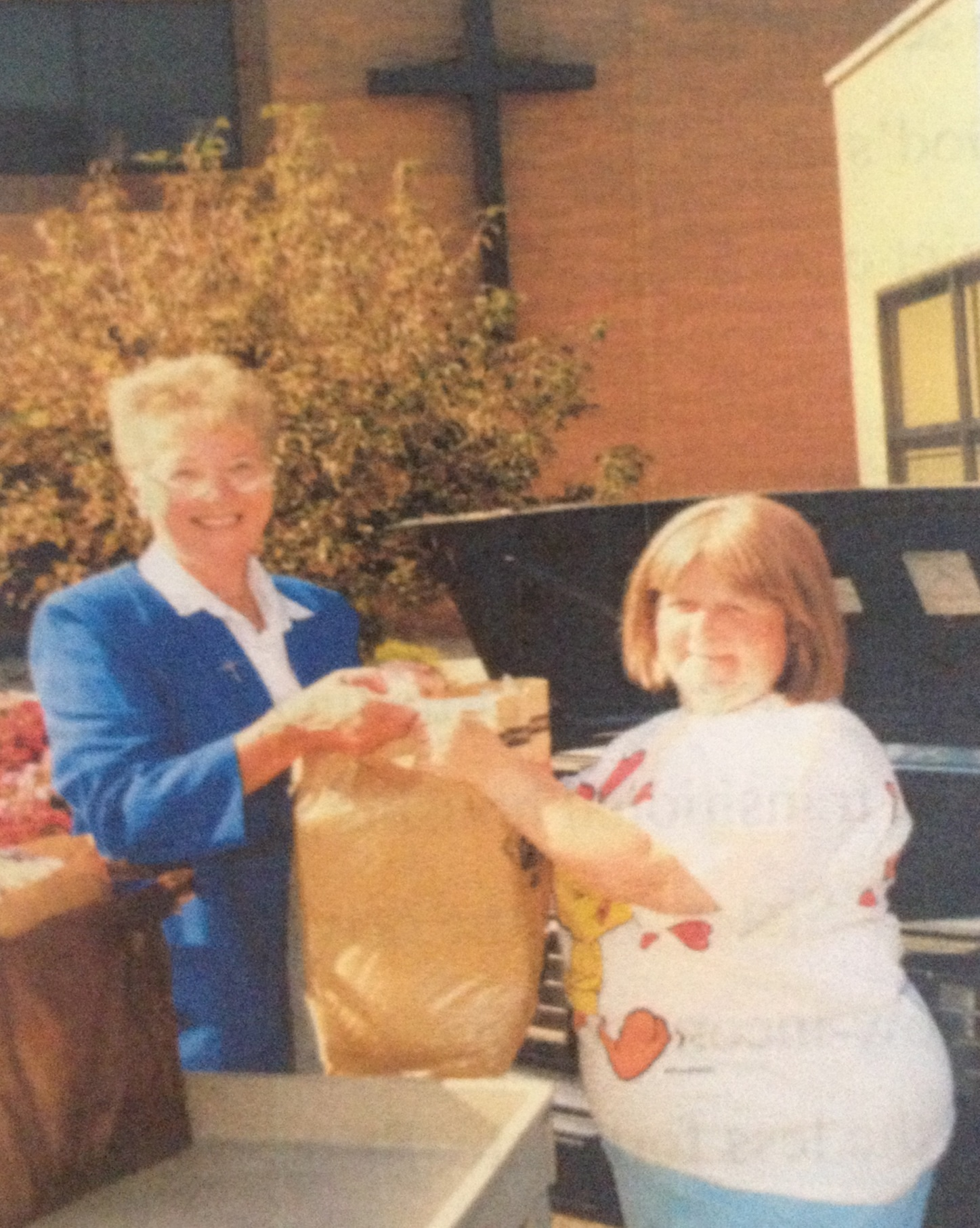 Sister Kathryn gave groceries to a client at the Holy Redeemer Food Cupboard opening in 1995.
