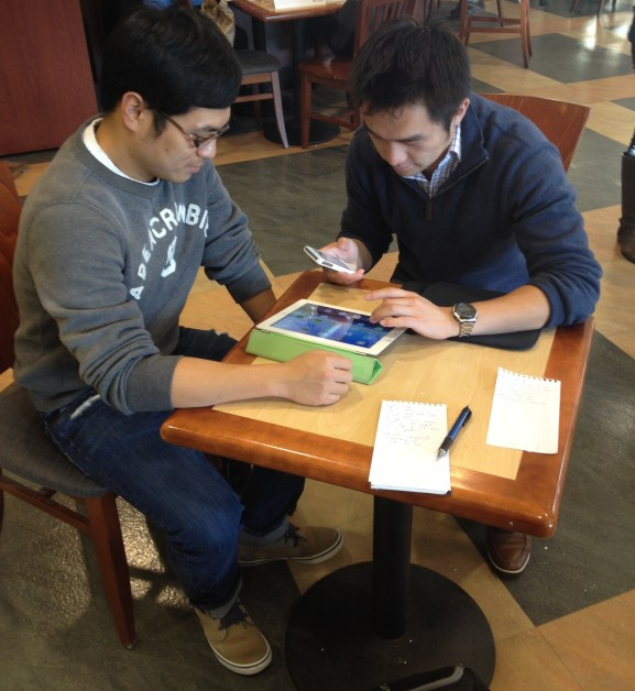 PicClick creators James Hui and Menglong Zhu look over their app on multiple devices.