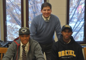 Roman Catholic head coach Chris McNesby stands in support of his two seniors, Garner, left, and London, right, and their college commitments.