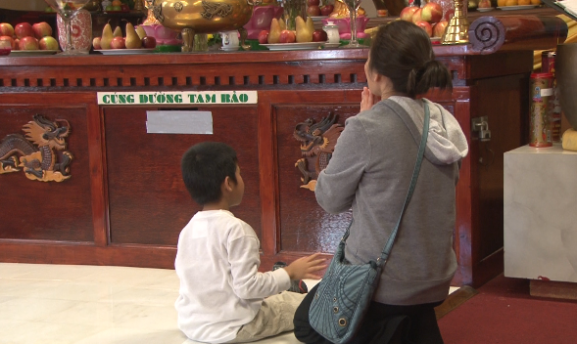 The tour stopped at a Buddhist Temple where people sat in prayer.