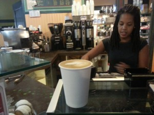 High Point Cafe barista serves a latte to a patron at the Allen's Lane Train Station shop.
