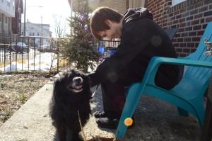 Green petting his dog Gem on their street in Roxborough.