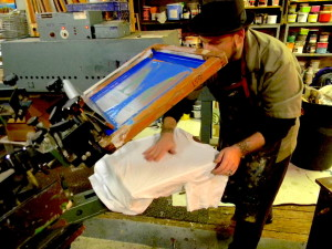 Potash works with a silk screen printing press to create a Philadelphia Neighborhoods t-shirt.