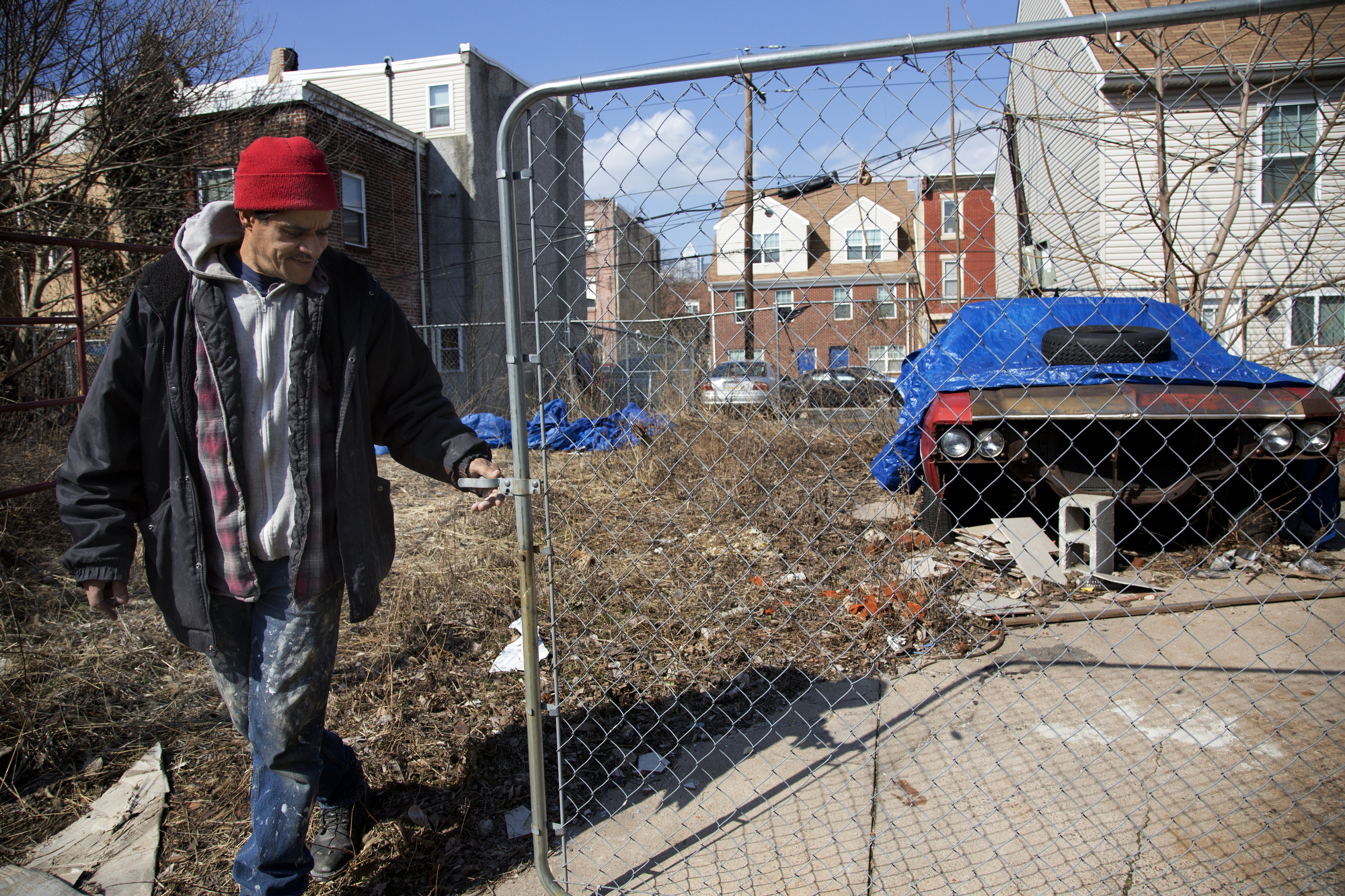 Mark Watts closes a gate to the yard of a home he is renovating on the 1100 block of South 15th Street in Philadelphia, March 20, 2014.