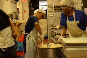 Volunteers scurried around the kitchen to prepare meals for the day.