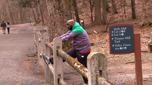 A jogger stretched before going on a run in the Wissahickon Valley Park.