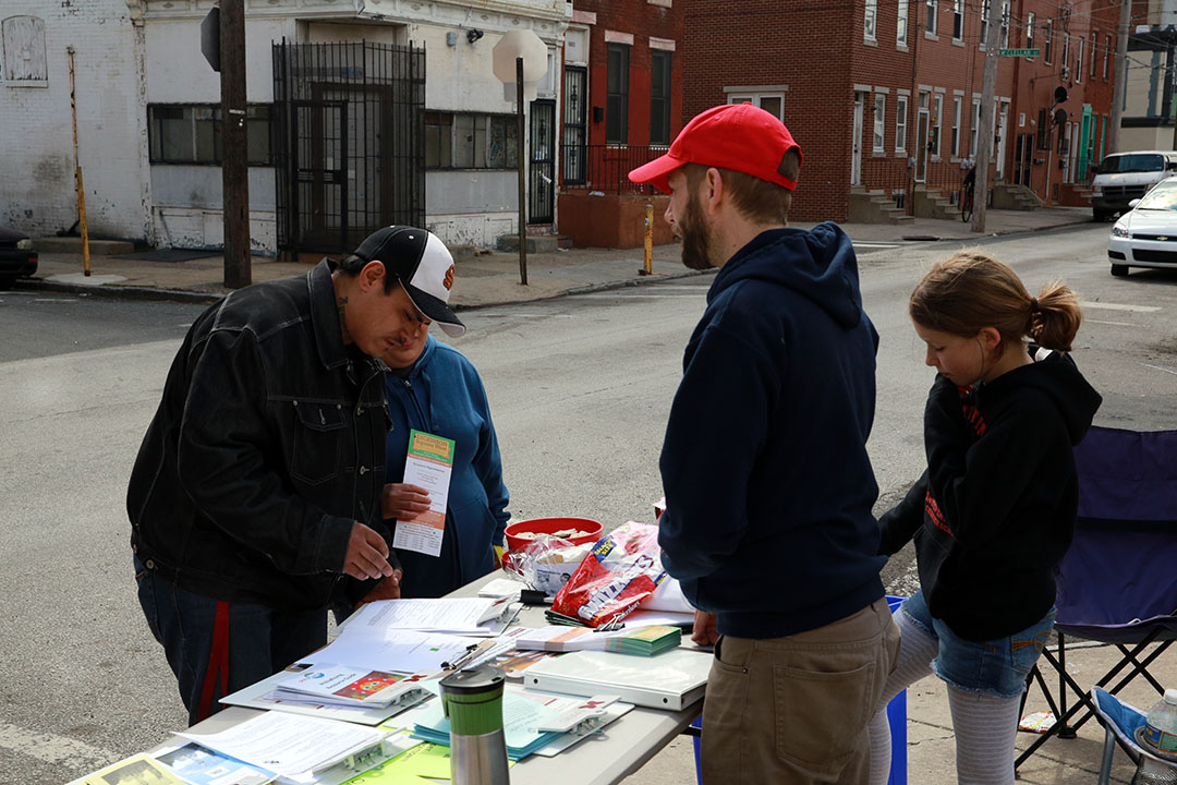 Neighbors filled out membership forms for the civic association and collected cleaning supplies at tables, located on South Fifth Street at Reed and Moore streets