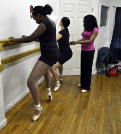 Candace Stanford, ballet and pointe instructor, help the girls warm up before class.
