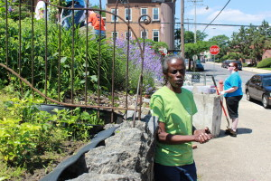 A local block captain stands  greets volunteers tending to garden next to her home.