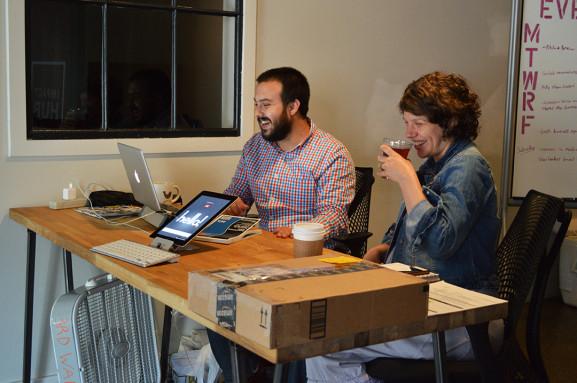 Etan Brandt-Finell and Laurel Klein share a laugh at Impact Hub's front desk.